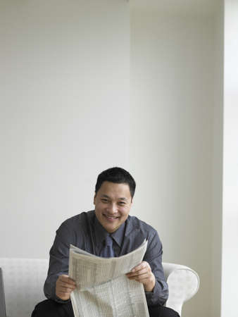 searcher: Young businessman reading a newspaper