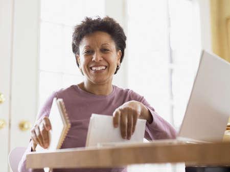 Frau mittleren Alters, lächelnd für die Kamera an ihrem Schreibtisch LANG_EVOIMAGES