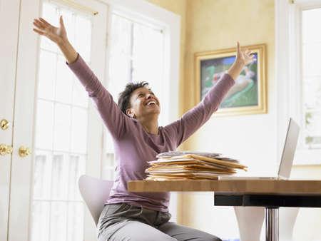 middleaged: Middle-aged woman celebrating at her desk LANG_EVOIMAGES