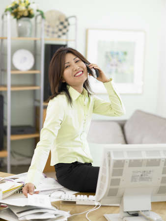 technology: Businesswoman talking on the phone at her desk LANG_EVOIMAGES