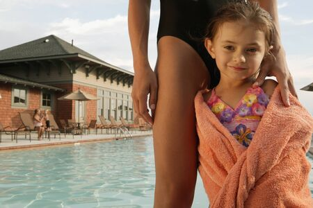 bathtowel: Young girl wrapped in a towel by swimming pool