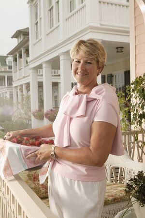 mischievious: Mature woman holding basket of strawberries