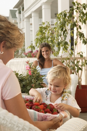 Woman offering strawberries to young child Stock Photo