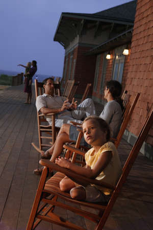 toiling: Family sitting in wooden rocking chairs at dusk