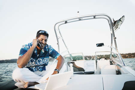 Young man talking on his cell phone and using a laptop on a boat Stock Photo
