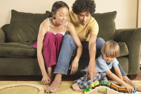 americal: Father and mother sitting on a couch with their son playing with toys on the ground LANG_EVOIMAGES