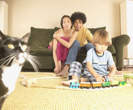 americal: Mother and father sitting on a couch with their son playing with toys on the floor