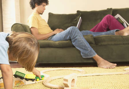 family: Father sitting on a couch working on a laptop with his son playing on the ground LANG_EVOIMAGES