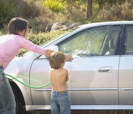 seres vivos: Madre e hijo lavando un coche con una manguera de jard�n