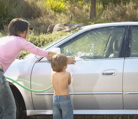 Mother and son washing a car with a garden hose LANG_EVOIMAGES