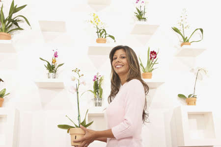 gratifying: Young woman holding potted flowers