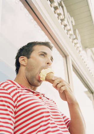motioning: Young man eating an ice cream cone LANG_EVOIMAGES