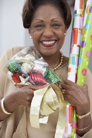 mischievious: Mature woman holding present-wrapping utensils LANG_EVOIMAGES