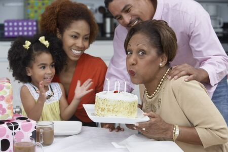one mid adult woman only: Mature woman blowing out the candles on her birthday cake