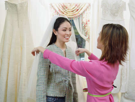 shopping buddies: Young woman wearing a veil in a bridal boutique