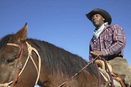 vaquero: Hombre joven en un traje de vaquero que monta un caballo