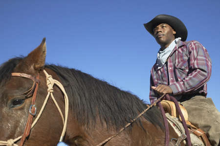 quarter horse: Young man in a cowboy outfit riding a horse