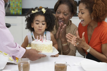 african american mother and daughter: Young girl blowing out the candles on her birthday cake