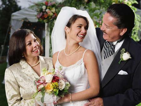 Braut posiert für die Kamera mit ihren Eltern LANG_EVOIMAGES