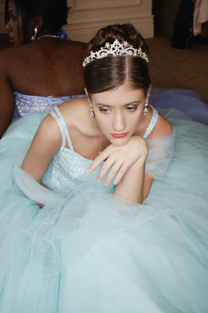 eveningwear: Teenage girl sitting alone at formal dance