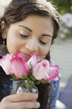 delighted: Teenage girl smelling pink roses
