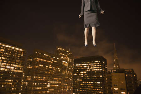 nite: Businesswoman floating above the city LANG_EVOIMAGES