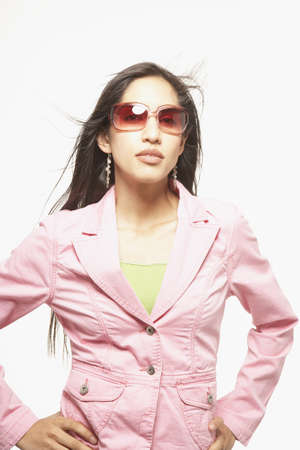 idealistic: Young woman posing for the camera in sunglasses and a coat
