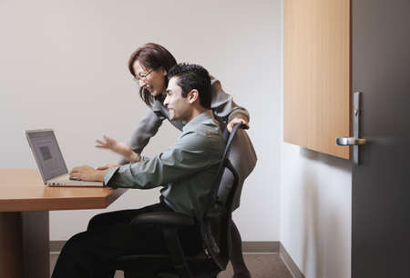 Businesspeople using a laptop in office area Stock Photo
