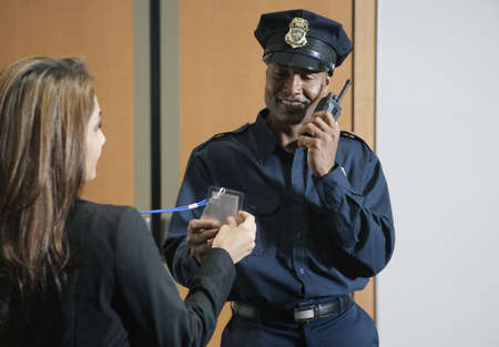 portraiture: Security guard checking businesswomanís credentials