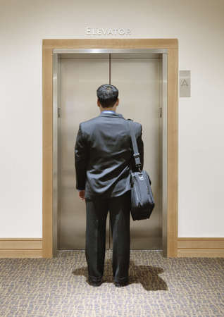 toiling: Businessman waiting for an elevator LANG_EVOIMAGES
