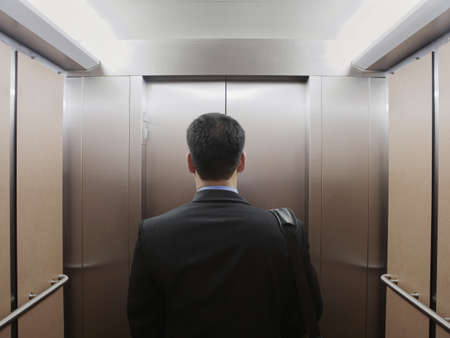 toiling: Businessman standing in an elevator LANG_EVOIMAGES