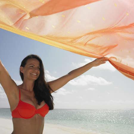 honeymooner: Joven mujer con un pareo en la playa LANG_EVOIMAGES