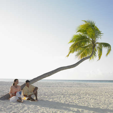 honeymooner: Couple reading at the beach
