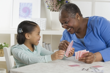 Senior woman playing cards with her granddaughter