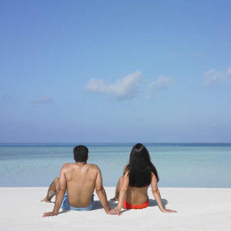 honeymooner: Pareja sentada en la playa  LANG_EVOIMAGES