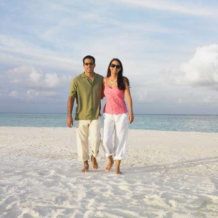 honeymooner: Couple walking on the beach LANG_EVOIMAGES