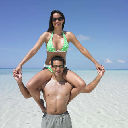 vacationing: Man carrying his girlfriend on his shoulders at the beach LANG_EVOIMAGES
