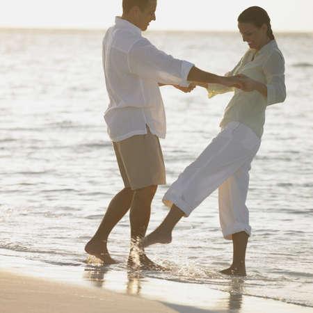 honeymooner: Pareja jugando en las olas en la playa