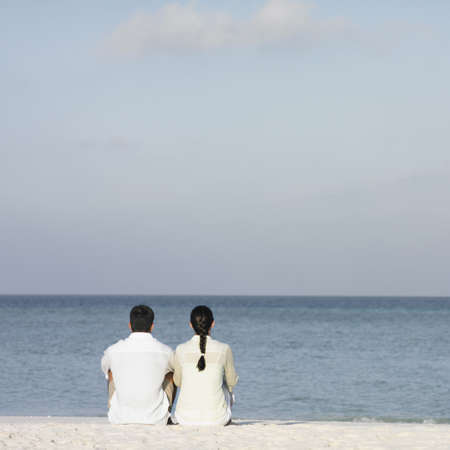 honeymooner: Pareja sentados juntos en la playa