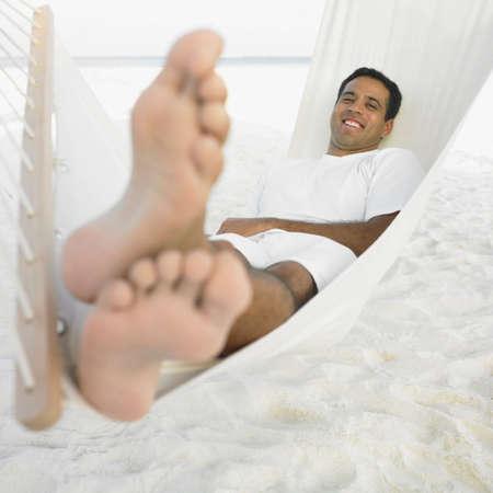 slumbering: Young man relaxing in a hammock