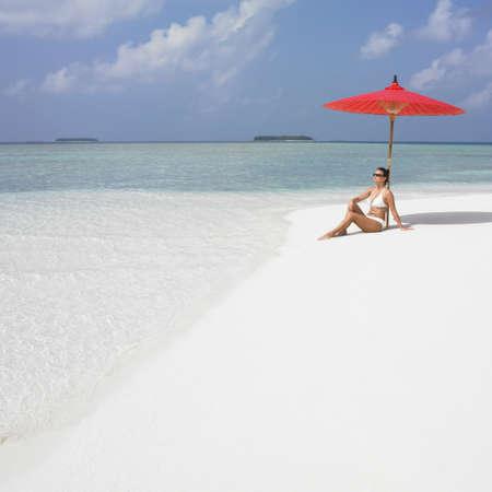 honeymooner: Joven mujer sentada bajo una sombrilla en la playa