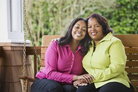 casualness: Mother and daughter smiling on a porch swing LANG_EVOIMAGES
