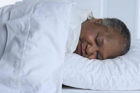 mid life: Senior woman asleep in bed