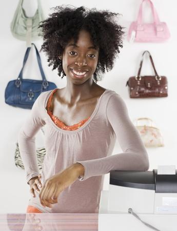 femme africaine: Femme souriante employ� derri�re le comptoir LANG_EVOIMAGES