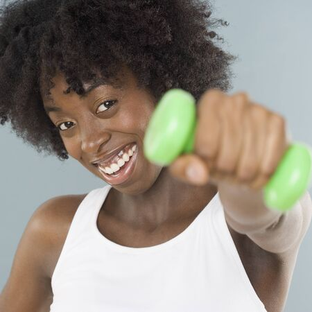exerting: Young woman lifting weights