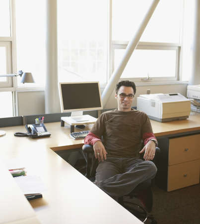 longshot: Businessman relaxing at his desk