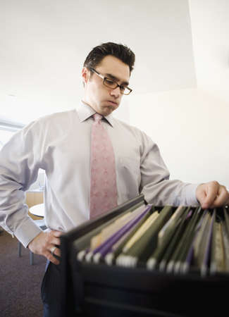 toiling: Businessman sorting through file cabinet LANG_EVOIMAGES