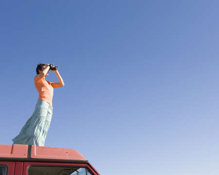lighthearted: Woman using binoculars on roof of car