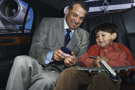 ostentatious: Businessman showing his son a gadget