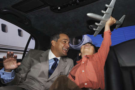poppa: Father and son playing with an airplane in a limo